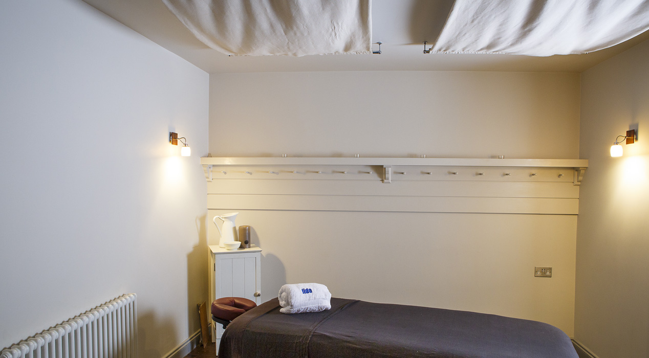 White shaker pegs under a shelf in a relaxing therapy space by Haldor Construction