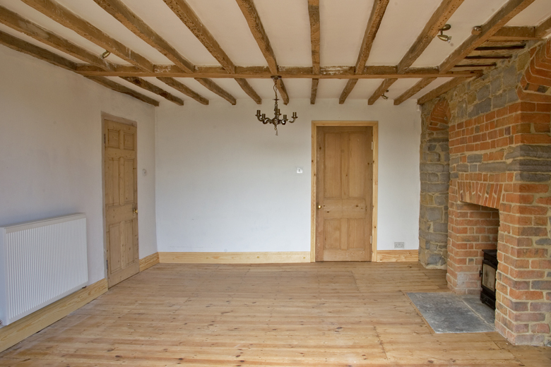 Lime plaster interior with exposed beams by Haldor Construction