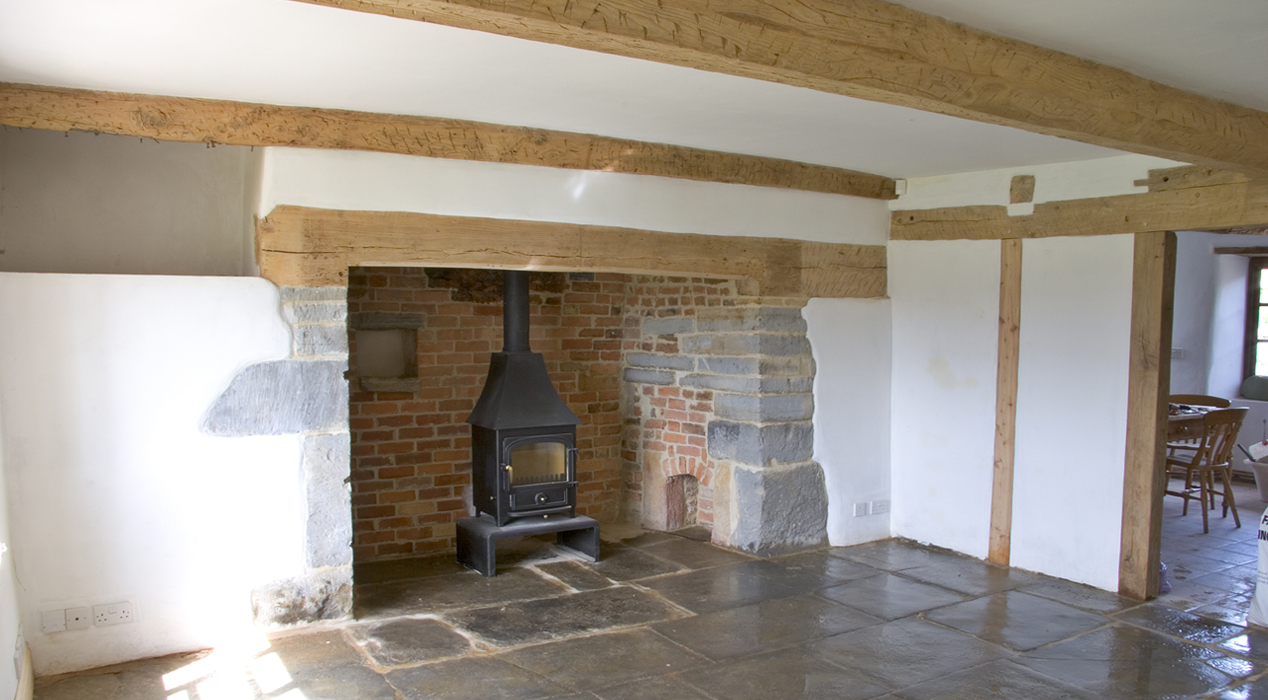 Plastering in a house with wooden beams. Showing stone floor and wood burner.