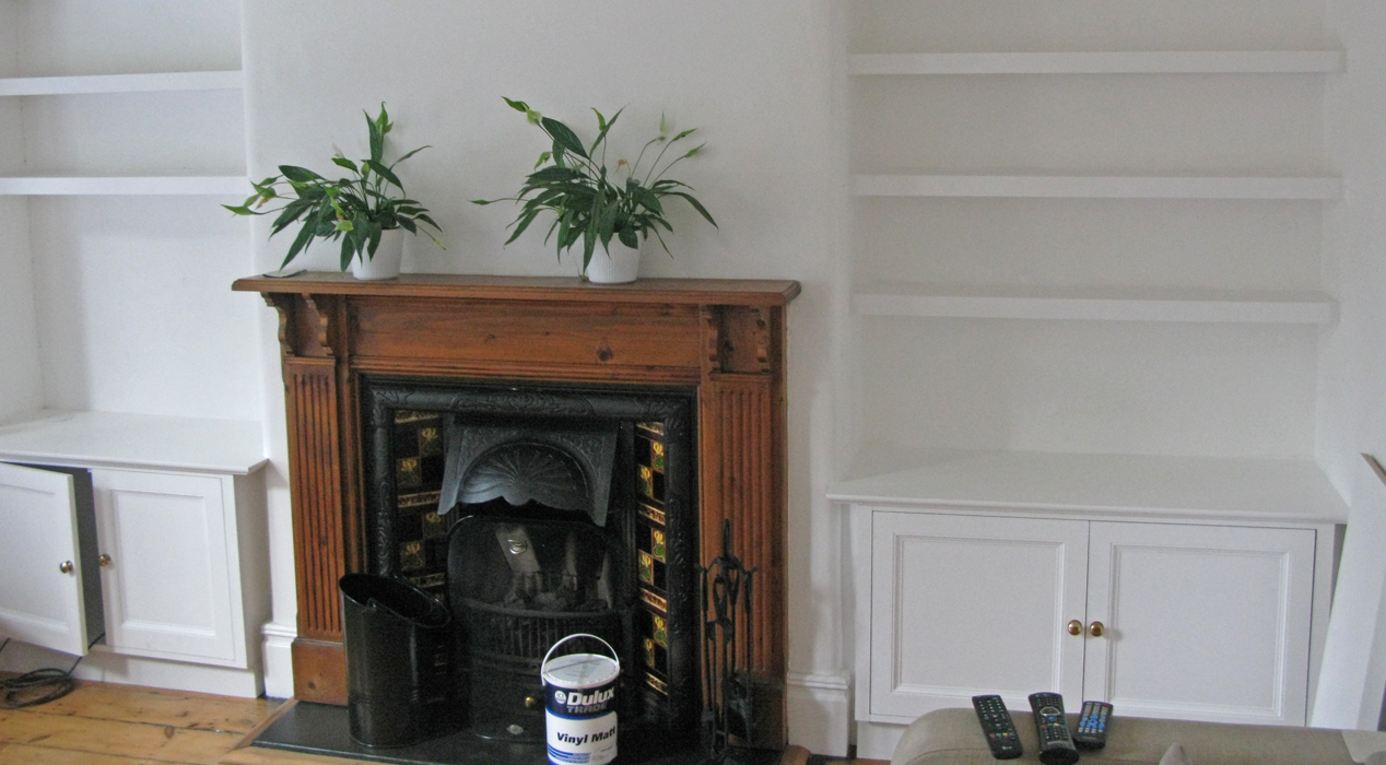 Carpentry by Haldor Construction. Bookshelves and built in cupboards either side of a Victorian fireplace.